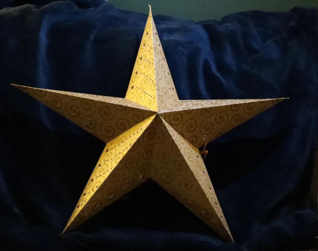 A large gold coloured paper star decorated with gold spirals and star-shaped cut-out sections rests against a dark blue backdrop.