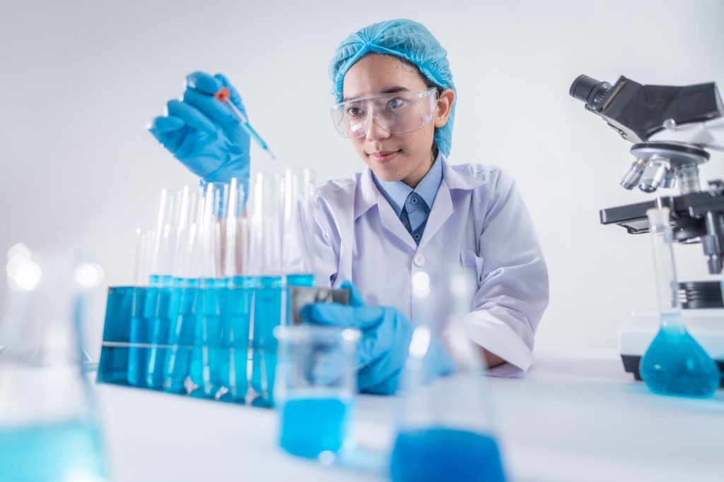 a lab coat, safety glasses, and a  blue cap covering their hair uses an eye dropper to add liquid to a series of large test tubes filled with blue liquid. Beakers and other science-related containers filled with containing the same liquid sit on their work surface. A microscope sits nearby.