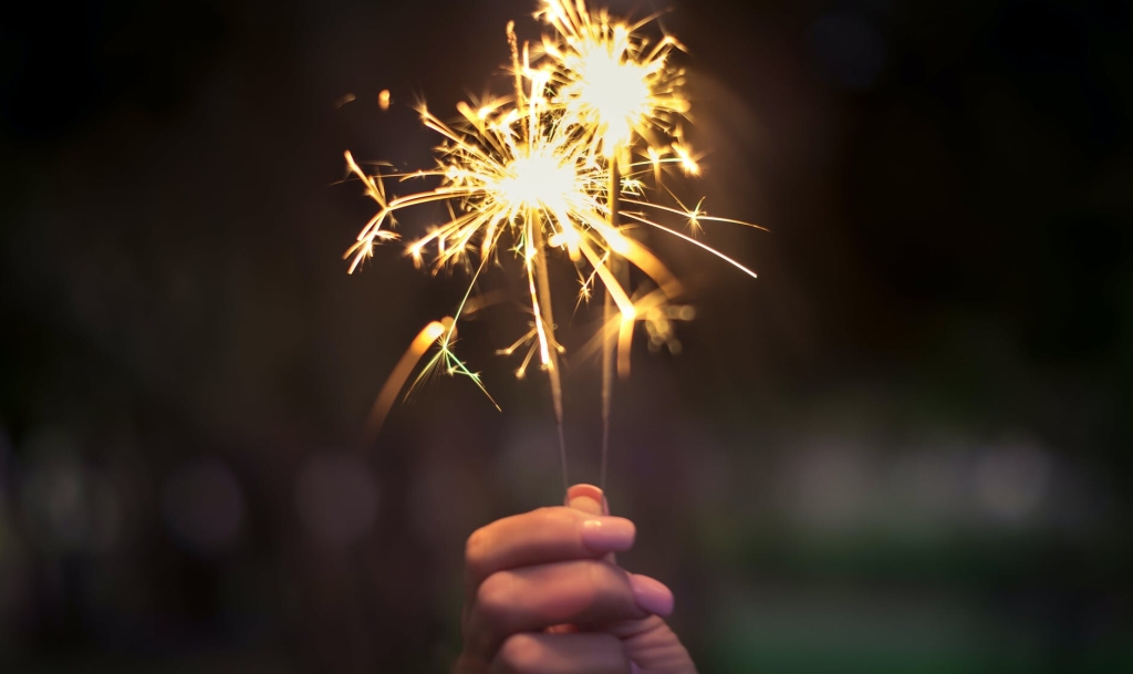 A  person's hand holding    a lit sparkler   that is generating star shaped sparks all around its top half. The background is blurred.