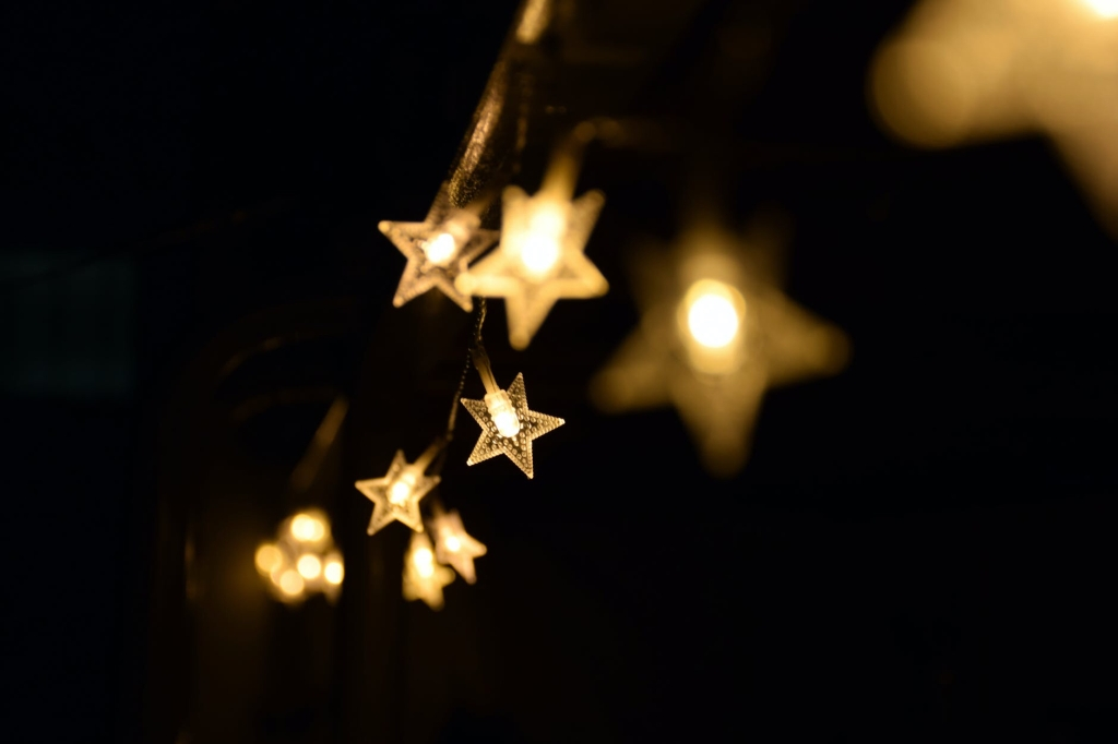 Image Description: A string of gold star-shaped lights extend into the distance. Some stars are in focus and some are not. the background is dark.