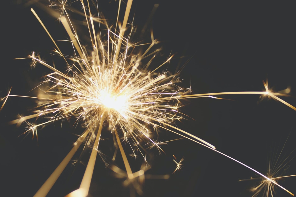 Image description: a gold sparkler (hand-held firework) is emitting star shapes in all directions.​