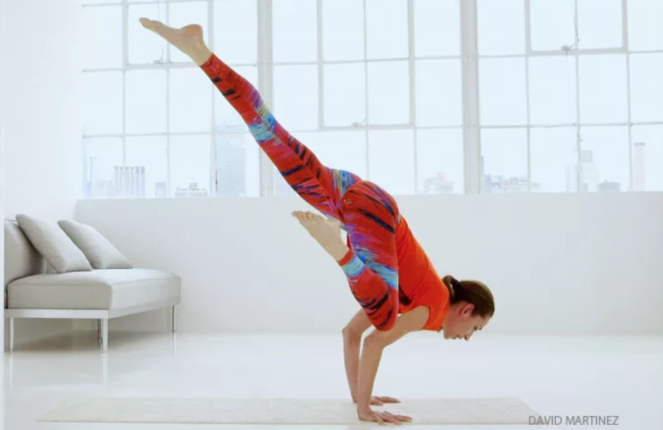 A woman in an advanced balance pose, wearing super-cute red, blue and black geometric print leggings.