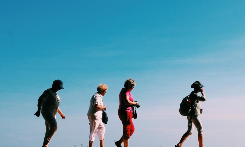 Four women walking, against a blue sky.