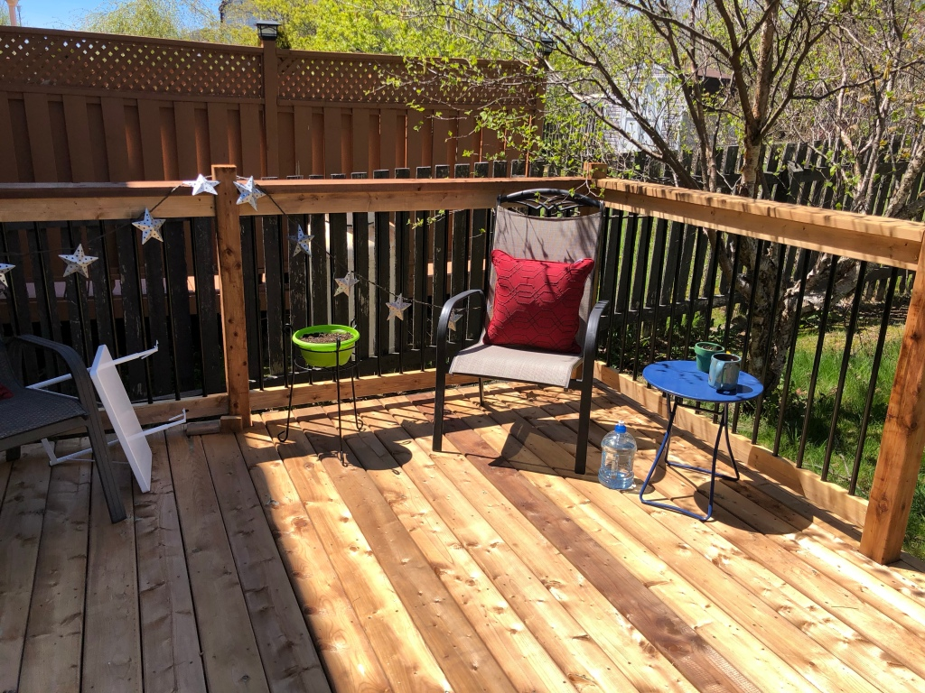 A photo of the corner of a wooden back deck, a lawn chair and two upright tables can be seen. A third table lies on its side on the left of the photo.