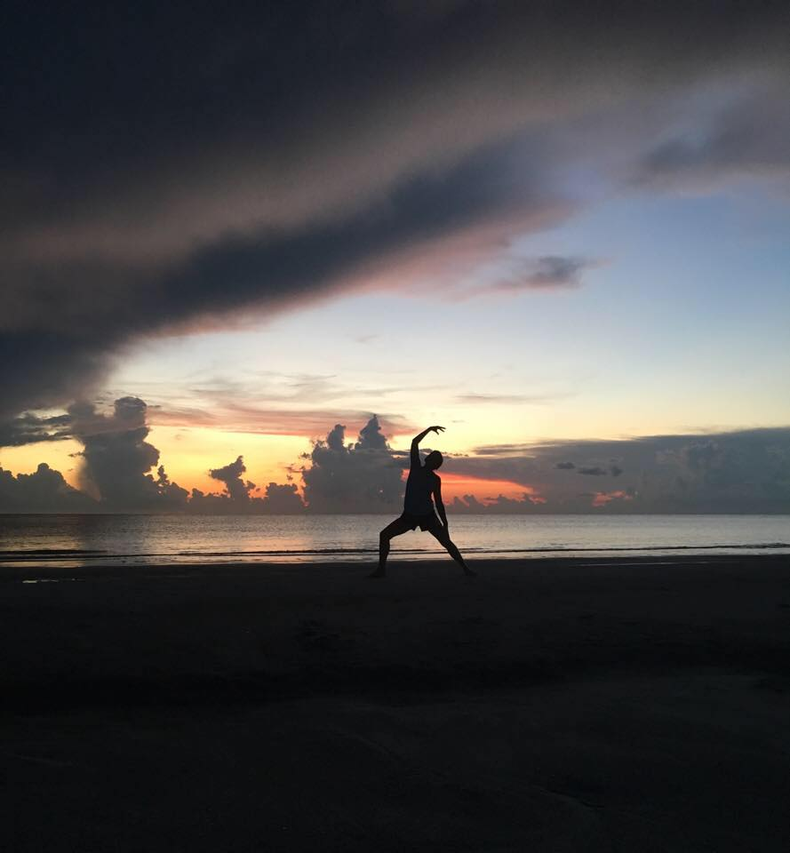 A silhouette of a person doing yoga on a beach at dusk.