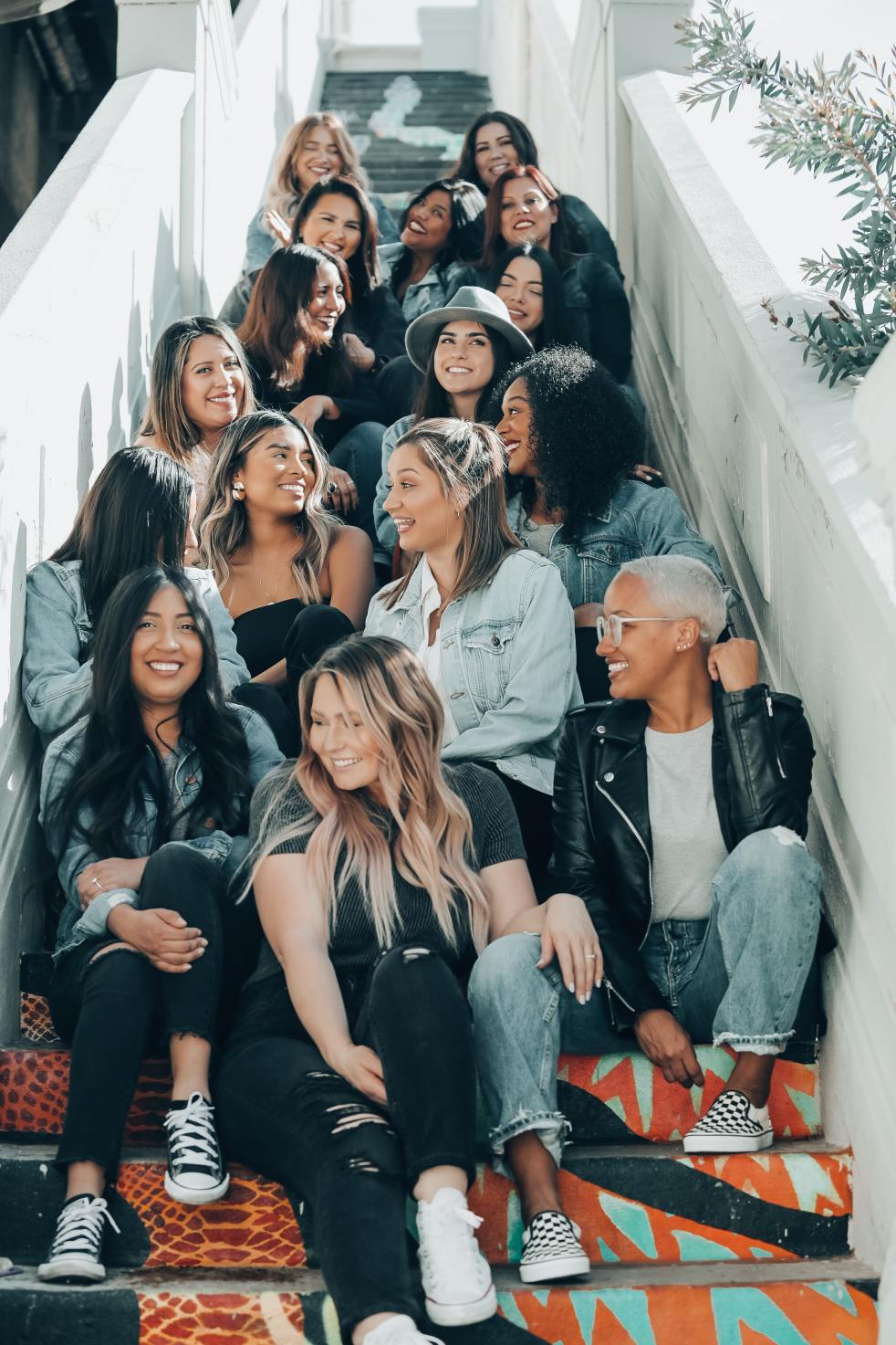 A group of women sitting on a staircase, looking happy with each other.