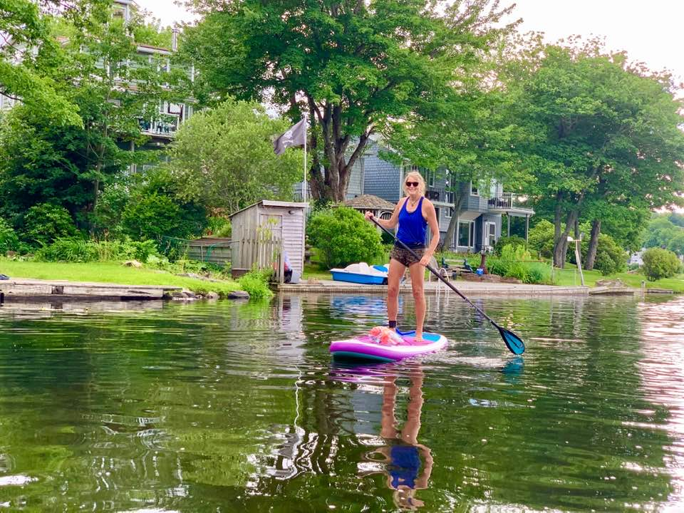 A woman stands on a paddleboard, floating on a body of water. She is holding an oar.