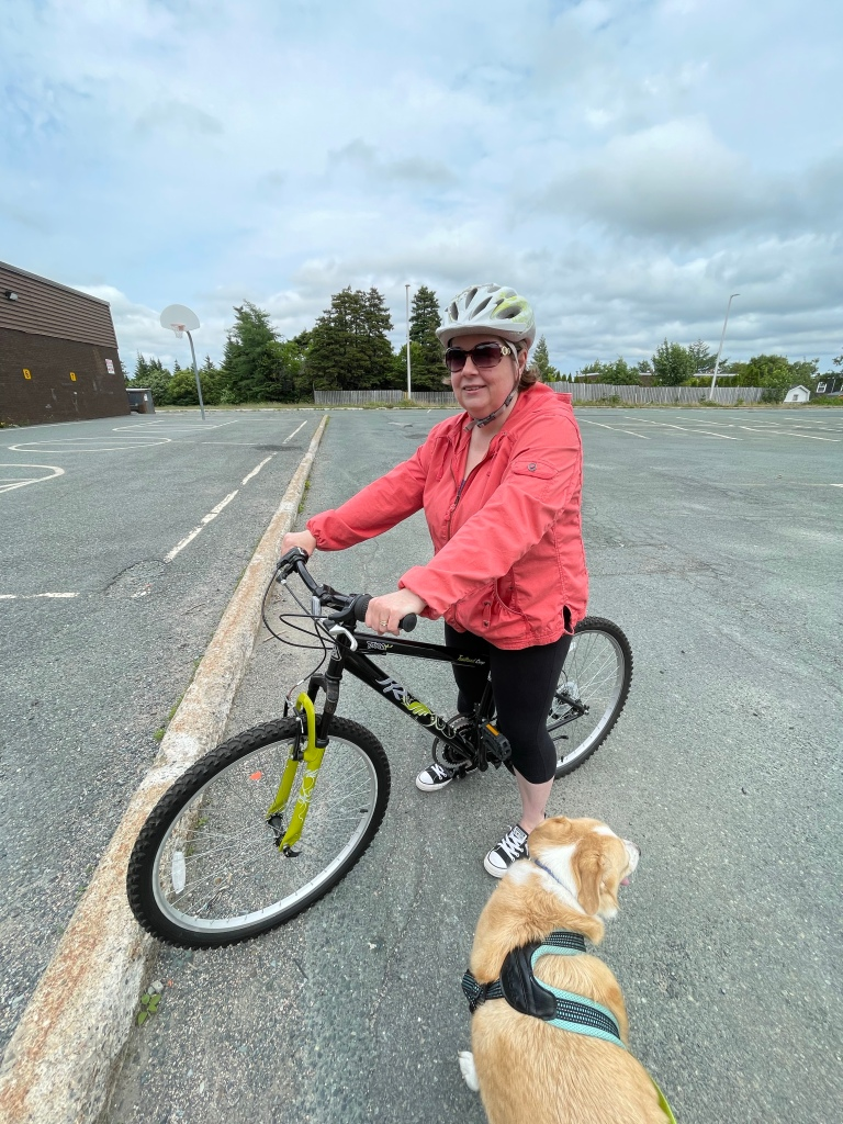 A woman stands astraddle a black bicycle in a parking lot. She is facing the camera. There is a light-haired dog in a harness at the bottom of the image.