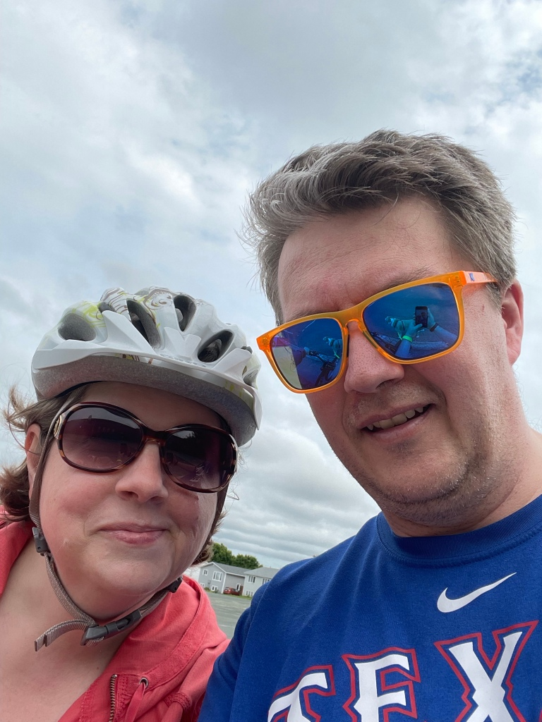 A 'selfie' of two people in sunglasses. The person on the left is wearing a bike helmet.