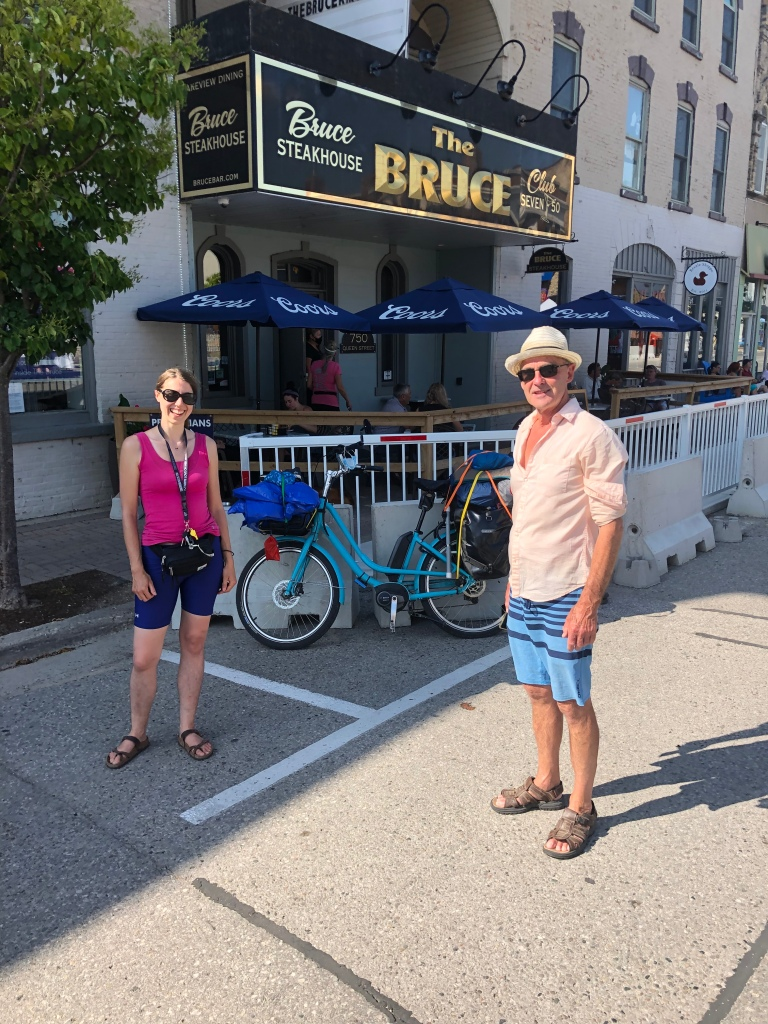 Mike and I are standing in the foreground with my bike between and behind us. In the background is The Bruce Steakhouse.