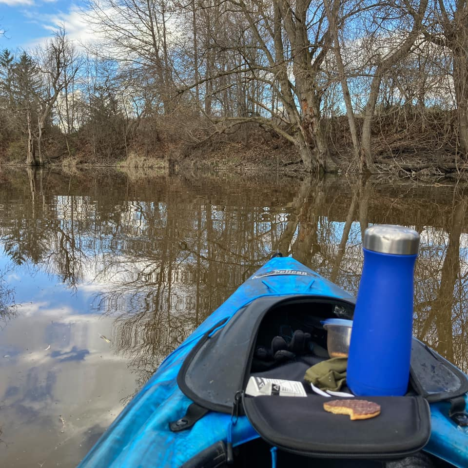 The front of a blue kayak sits on calm water. There is a blue thermos and a half-eaten cookie sitting on the top of a small zippered compartment.