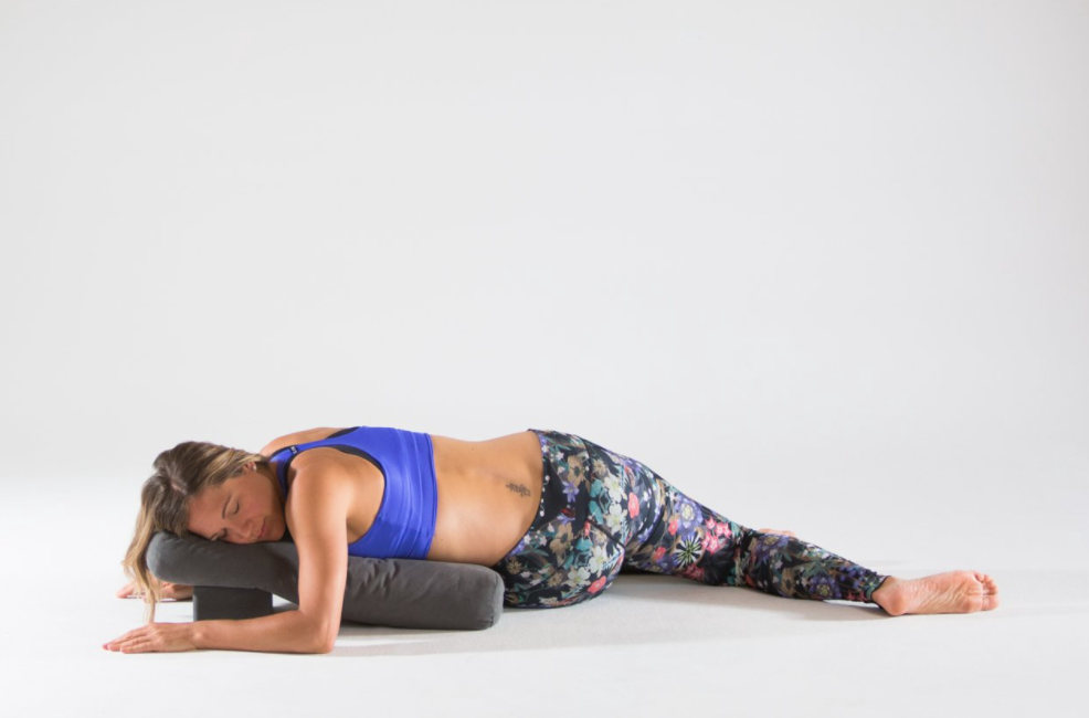 Woman doing a restorative side twist pose with her chest down on the mat and her head turned to the side.