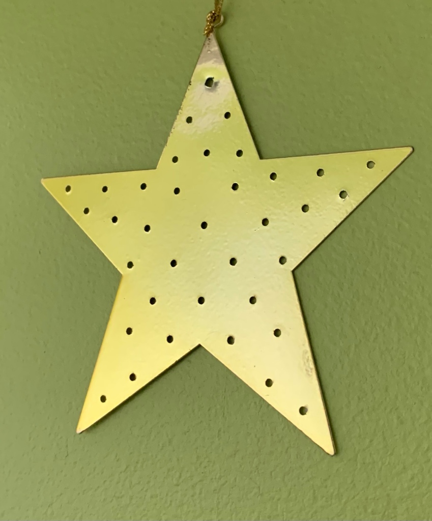 A gold-coloured star-shaped metal decoration hangs on a light green painted wall.