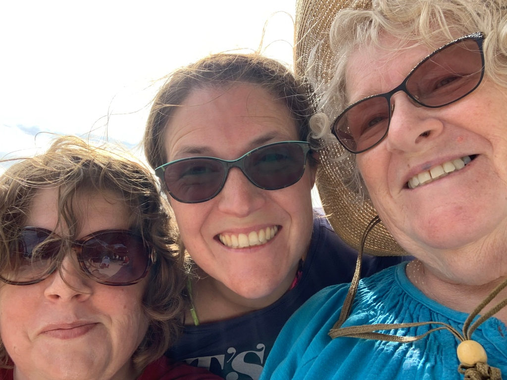 Image description: A 'selfie' style photo of Christine, Denise, and Carol-ann (a.k.a. Mom.)  They are all wearing sunglasses, Denise and Carol-ann are smiling and Christine is smirking.