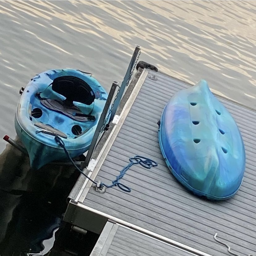 Image description: a bright blue fibreglass kayak is tied up at a small floating dock on a lake. The kayak cover rests on the dock and we can see the water all around the dock and the kayak.
