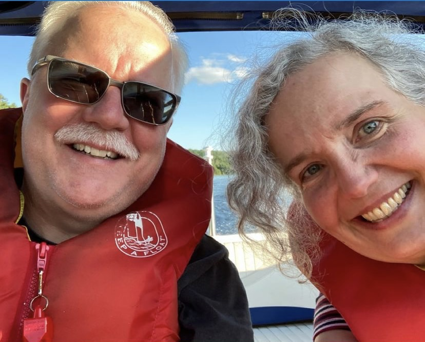 Image description: Two middle-aged adults in life jackets smile for the camera. Ann, on the right, has curly grey hair. Neil, on the left, has short grey hair and a moustache and he is wearing sunglasses. The deck of a boat and some lake water can be seen behind them.