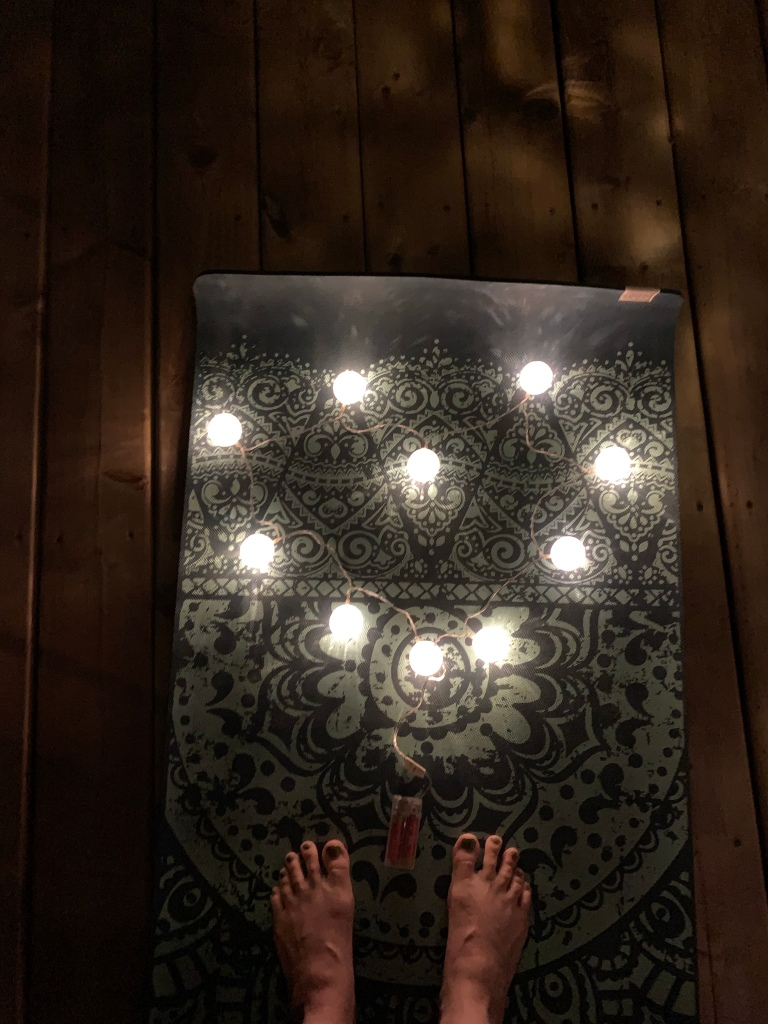 A nighttime photo on my patio string of round, white battery-operated lights are arranged in the shape of a heart on my blue yoga mat. My feet are visible on the mat below the lights,