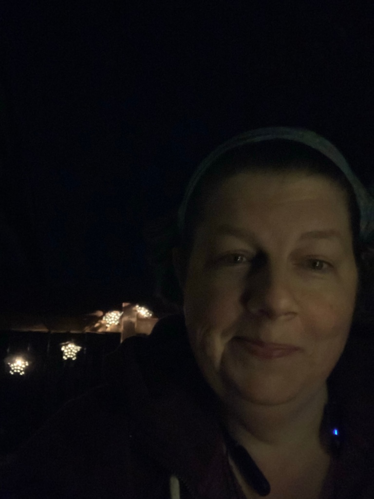 A dimly-lit photo of Christine outdoors at night. A string of star-shaped lights are visible over her shoulder.