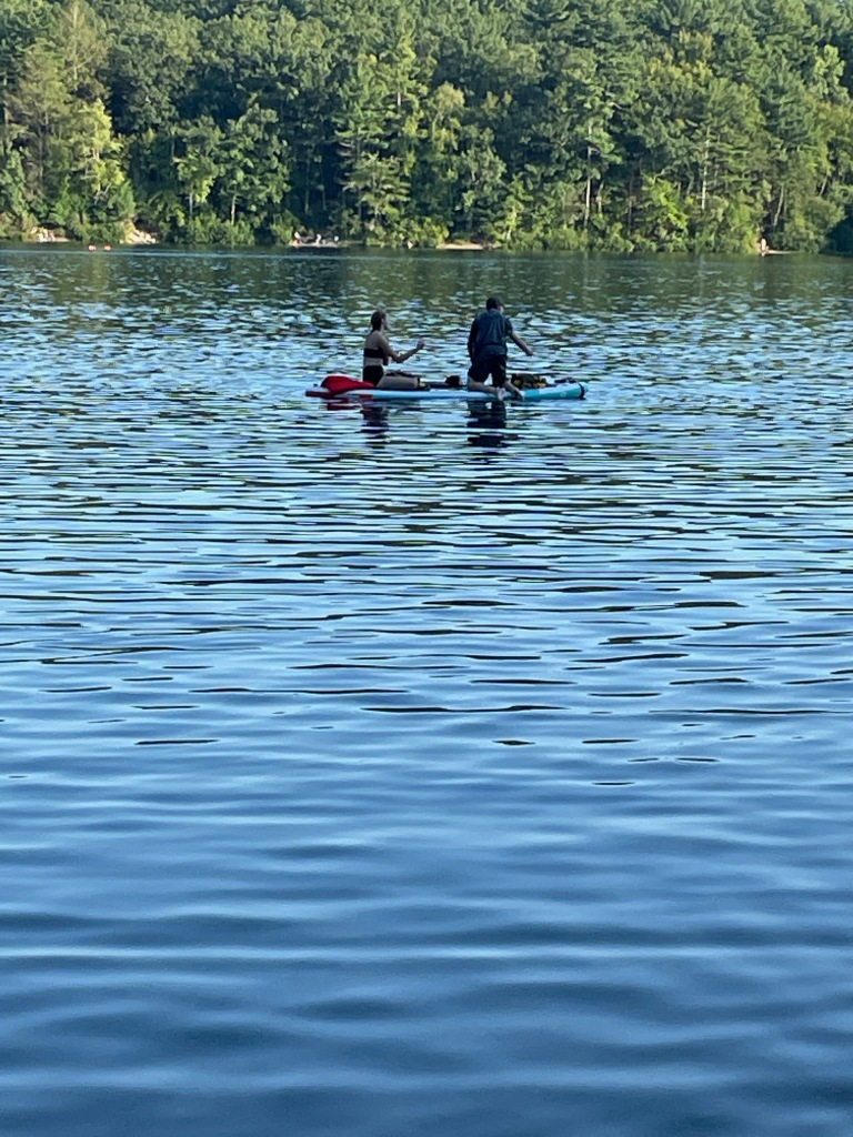 Two people are kneeling on a standup paddleboard.