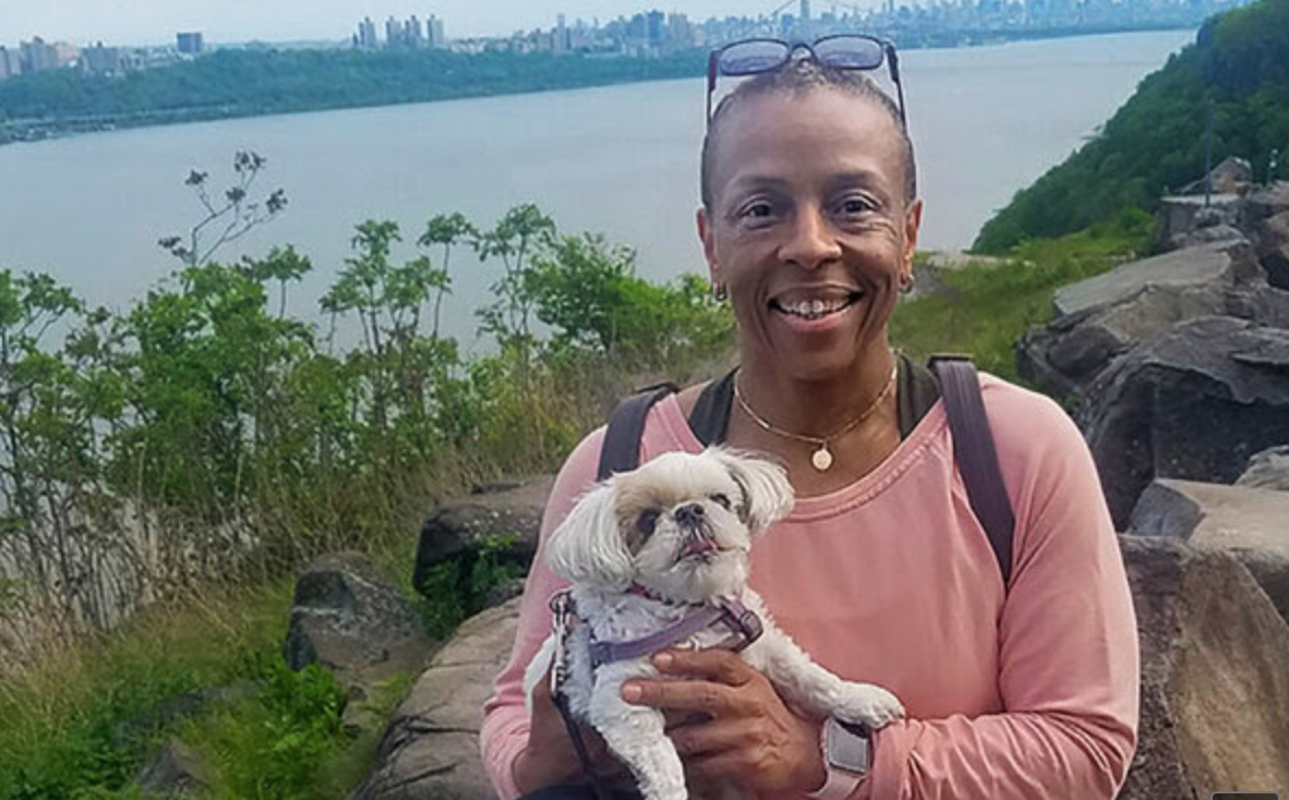Faith and her dog Moxie, standing on the Palisades, the Hudson River in the background.